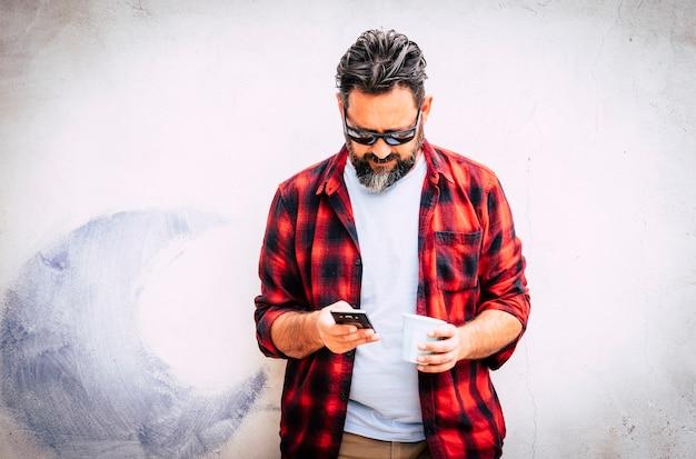 Hipster jonge blanke man met baard en rood shirt kijken naar de telefoon voor berichten of vrienden bellen