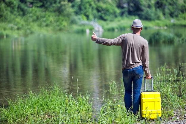 Hipster jonge man liftend langs een bergrivier met een gele koffer