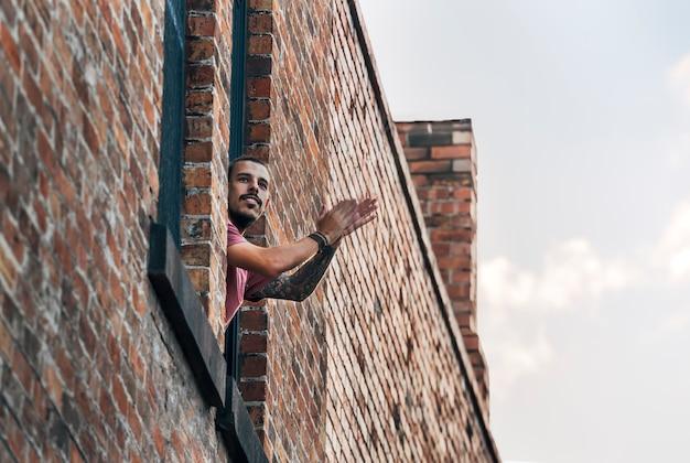 Hipster jonge mannelijke volwassene applaudisseren vanaf zijn balkon of raam om medische zorg te ondersteunen tijdens een pandemie van het coronavirus