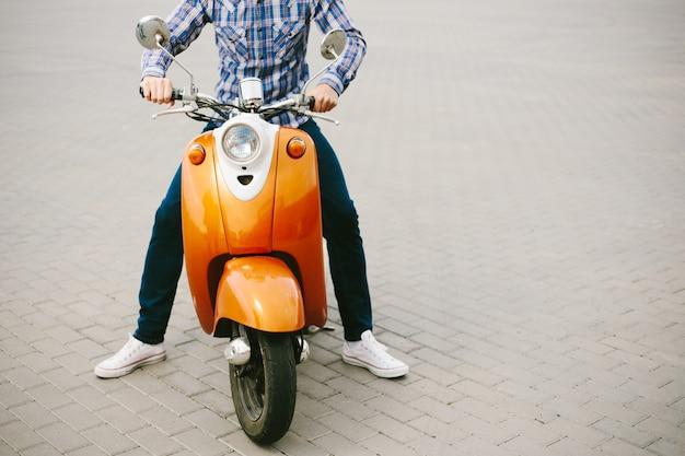 Hipster jongeman in helm rijdt op gele retro scooter in de stad