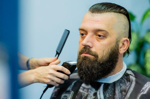 Hipster klant een bezoek aan de kapper. herenmode. bebaarde man na kapper. man hipster