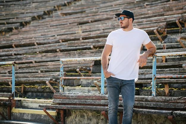 Hipster knap mannelijk model met baard, gekleed in een wit leeg t-shirt en een baseballpet met ruimte voor uw logo of ontwerp in een ongedwongen stedelijke stijl