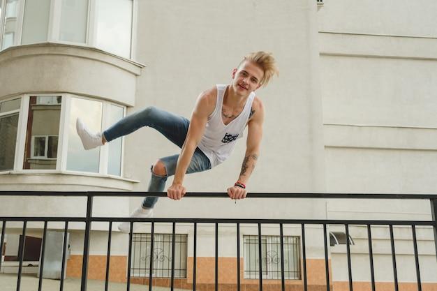 Hipster knappe blonde man man in stijlvolle zomer kleding in de straat