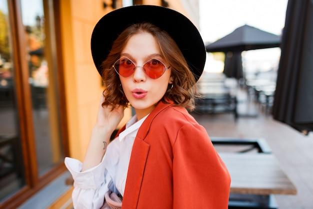 Hipster kortharig meisje die met opwindend gezicht knipogen. stijlvolle uitstraling. oranje jas en zwarte hoed.