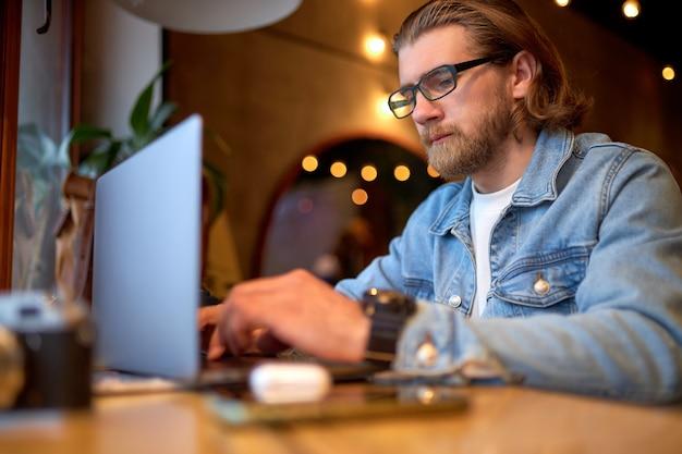 Hipster-levensstijl en creatieve werkruimte, zelfverzekerde man die op laptop in coffeeshop werkt