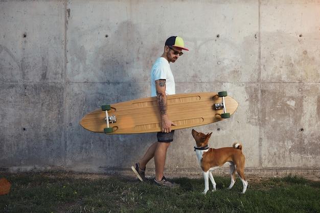 Hipster longboarder en een jonge bruine en witte basenji hond kijken elkaar naast een grijze betonnen muur