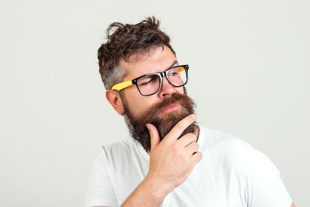 Hipster man denken, zijn baard aan te raken. bebaarde man in doordachte glazen