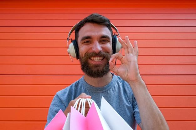 Hipster-man geniet van grote verkopen tijdens het winkelen op zwarte vrijdag