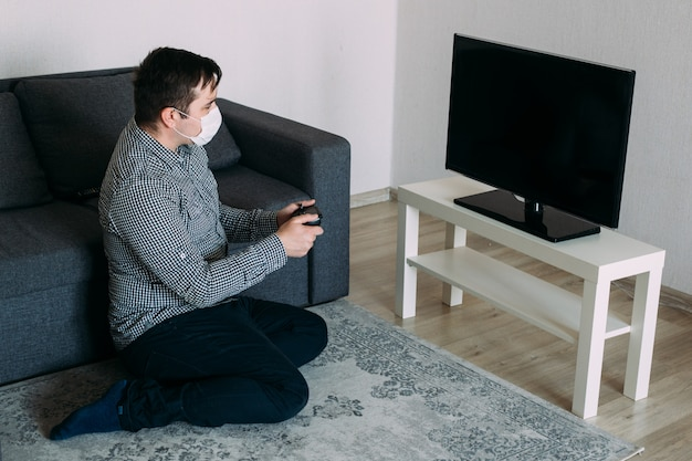 Hipster man in masker spelen met spelcomputer op tv