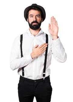 Hipster man met baard die een eed maakt