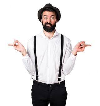 Hipster man met baard die naar de laterals wijst en twijfels heeft