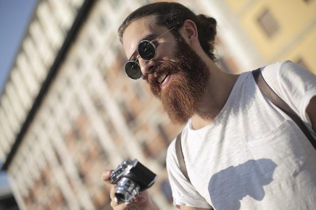 Hipster man met behulp van een camera