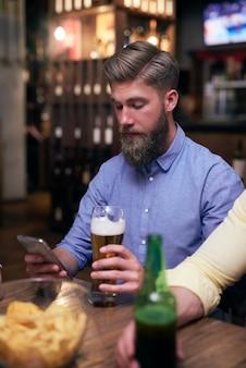 Hipster man met behulp van mobiele telefoon en bier drinken