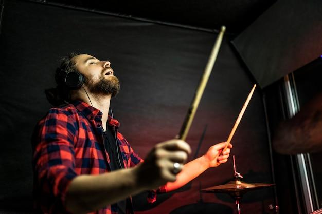 Hipster-man met de baard in koptelefoon speelt drum en zingt in de stereostudio