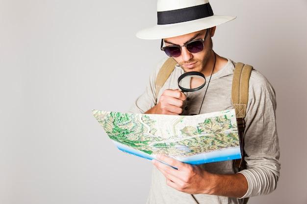 Hipster man met kaart en vergrootglas