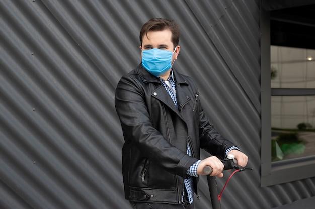 Hipster man met medische masker op elektrische scooter
