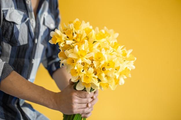 Hipster man op een gele achtergrond in een shirt en een boeket bloemen.