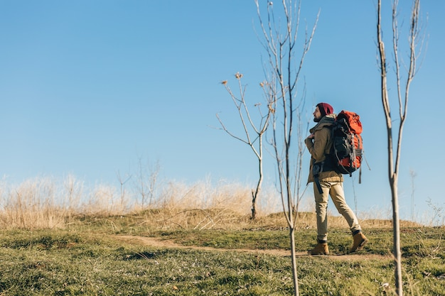Hipster man reizen met rugzak in herfst bos dragen warme jas, hoed, actieve toerist, natuur in koude seizoen verkennen