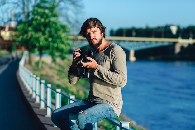 Hipster man schoot fotografie van hem filmcamera op straat publiek