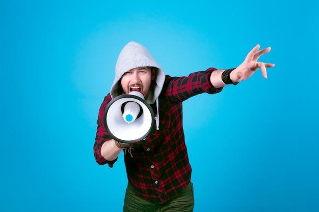Hipster man schreeuwt in megafoon, afbeelding op blauwe muur, concept activist in actie