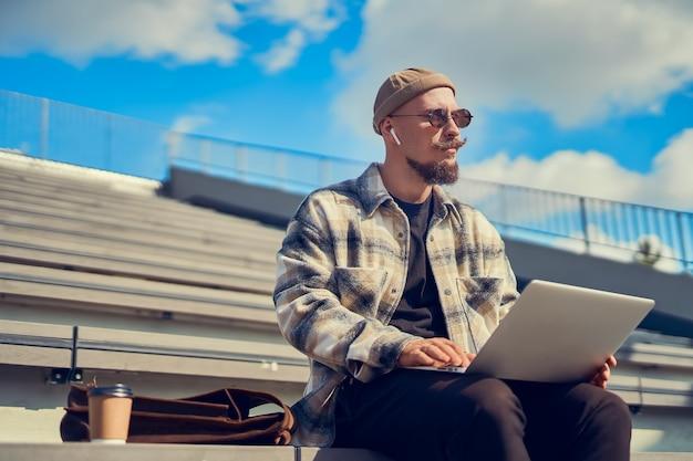 Hipster man zit buiten met koffie terwijl hij aan het bloggen is, online studeert en zijwaarts kijkt