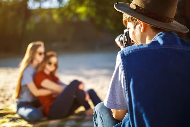 Hipster mannen in de hoed maakt foto's van zijn vriendinnen. een groep vrienden genieten van tijd op het strand. ze lachen en glimlachen. vriendelijke sfeer. jongens genieten van foto's. breng de zomer goed door.