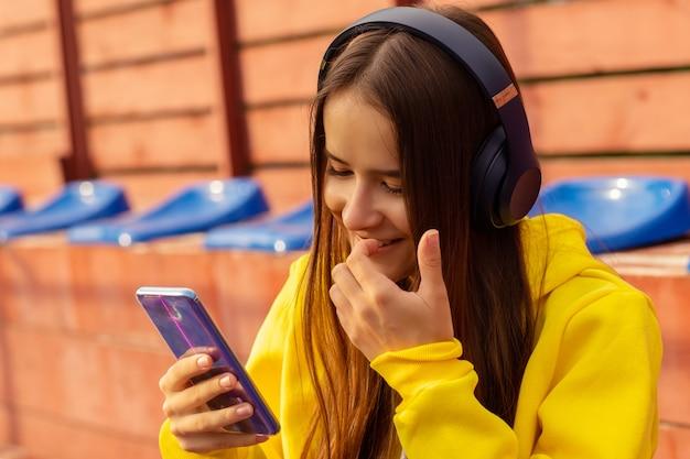 Hipster meisje geniet van favoriete muzieklied in draadloze hoofdtelefoons op een zonnige dag in het stadion