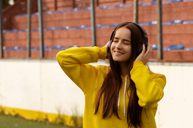 Hipster meisje in koptelefoon op straat luisteren naar muziek