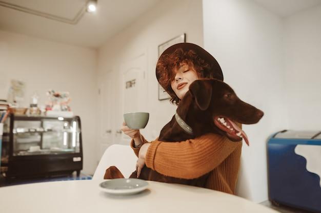 Hipster meisje in stijlvolle kleding en hoed knuffelt hond aan tafel in café en houdt koffiekopje in de hand