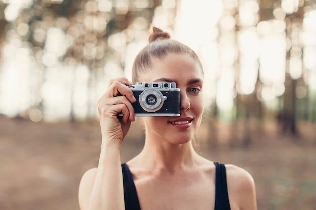 Hipster meisje met behulp van vintage fotocamera
