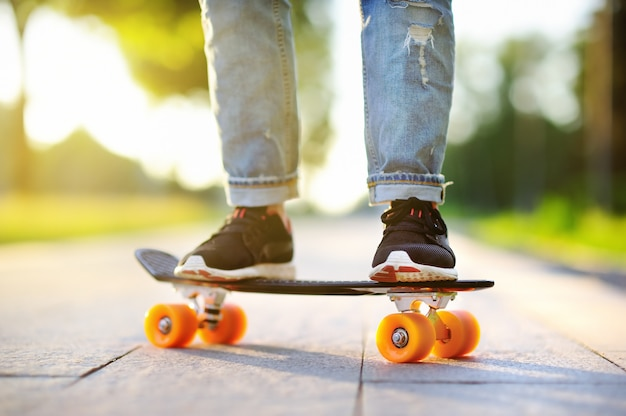 Hipster meisje met skateboard buitenshuis. close-up skateboarden. actieve sportieve vrouw plezier in park