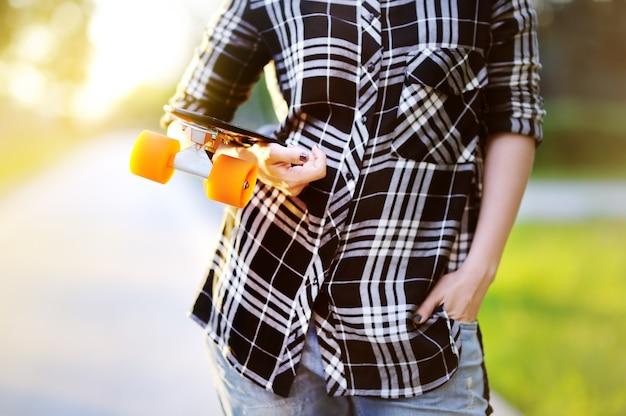Hipster meisje met skateboard buitenshuis. close-upskateboard in vrouwelijke hand. actieve sportieve vrouw plezier in park