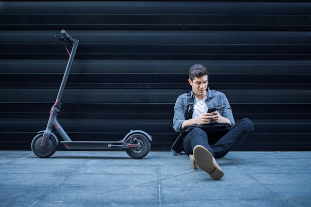 Hipster met behulp van slimme telefoon terwijl hij op de grond naast zijn elektrische scooter tegen zwarte muur zit