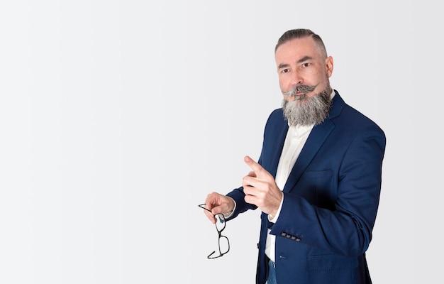 Hipster met grote baard en gekleed in blauwe jas en spijkerbroek, bril in zijn hand houden en indicatie geven
