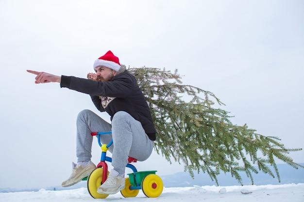 Hipster met kerstboom op witte sneeuw