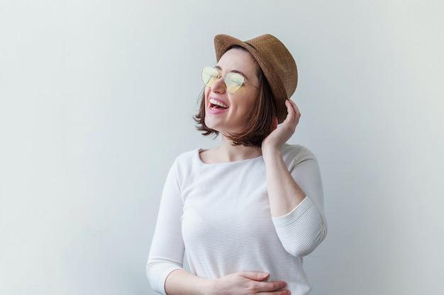 Hipster mode glimlachend meisje in trendy gele zonnebril en hoed geïsoleerd op wit