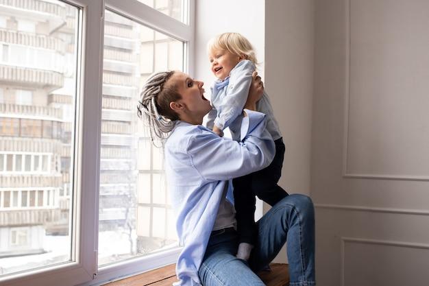 Hipster moeder met babyjongen zoon bij het raam zitten en spelen