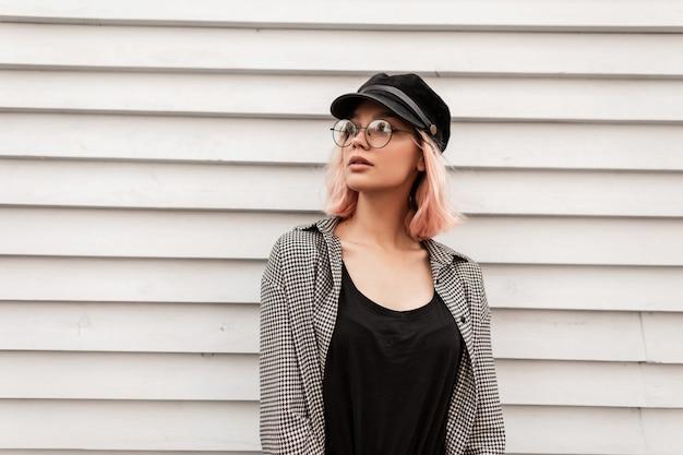 Hipster mooi jong kaukasisch meisje met schattig gezicht en roze haar in trendy vrijetijdskleding met bril en hoed staat in de buurt van houten muur achtergrond