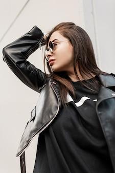 Hipster mooie coole vrouw met trendy zonnebril in fashion rock leren jas en zwarte sweater op grijze achtergrond wandelingen in de stad. stedelijk portret van een vrouwelijk model