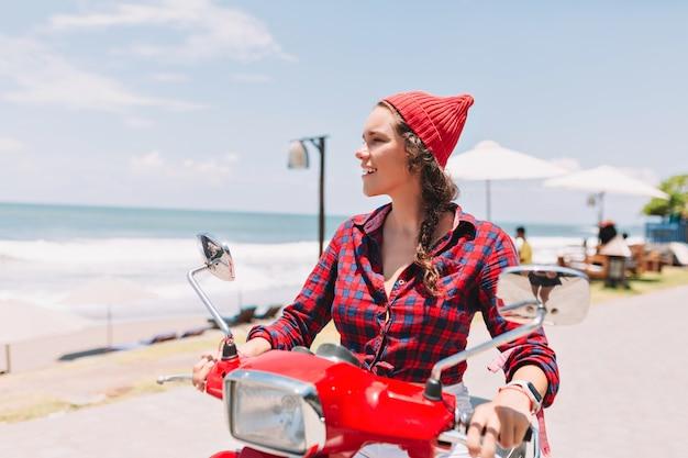Hipster mooie dame gekleed in geruite overhemd en rode pet rijdt op de rode fiets in zonlicht op de achtergrond van de oceaan met blauw water.