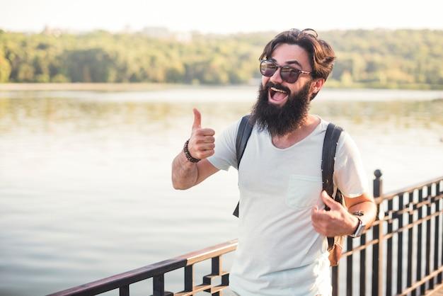 Hipster op vakantie naast meer