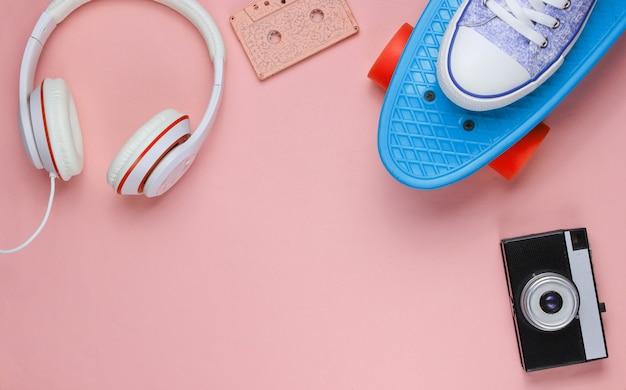Hipster-outfit. skateboard, koptelefoon, audiocassette, sneakers, retro camera op roze pastel achtergrond. creatief modeminimalisme. minimaal zomerplezier. pop-art. jaren 80. ruimte kopiëren. bovenaanzicht