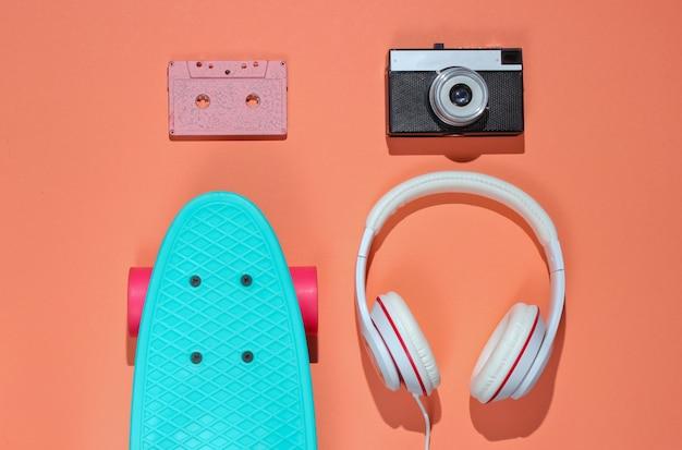 Hipster-outfit. skateboard met koptelefoon, audiocassette op koraalkleurige achtergrond. creatief mode-minimalisme. trendy retro jaren 80-stijl. minimaal zomerplezier.