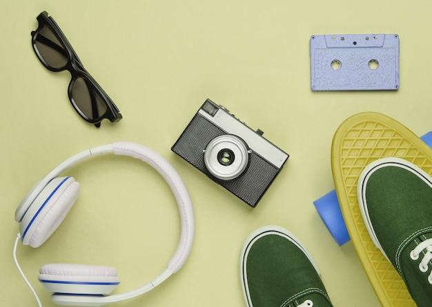 Hipster-outfit. skateboard met koptelefoon, audiocassette, retro camera en sneakers op groene pastelachtergrond. creatief modeminimalisme. minimaal zomerplezier. bovenaanzicht