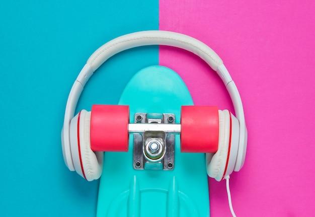 Hipster-outfit. skateboard met koptelefoon op gekleurde achtergrond. creatief mode-minimalisme. trendy oude modieuze stijl. minimaal zomerplezier. muziek concept. bovenaanzicht