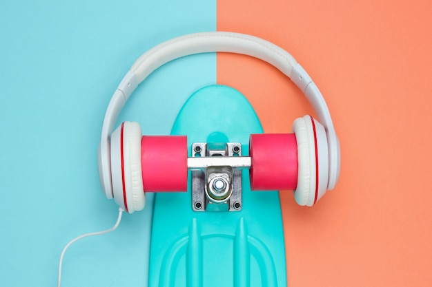 Hipster-outfit. skateboard met koptelefoon op gekleurde achtergrond. creatief mode-minimalisme. trendy oude modieuze stijl. minimaal zomerplezier. muziek concept.