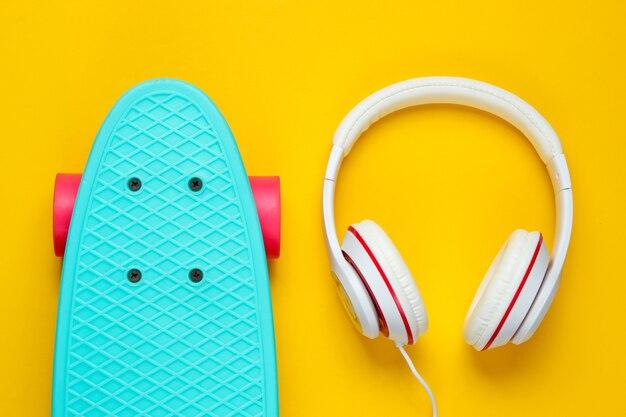 Hipster-outfit. skateboard met koptelefoon op gele achtergrond. creatief mode-minimalisme. trendy oude modieuze stijl. minimaal zomerplezier. muziek concept
