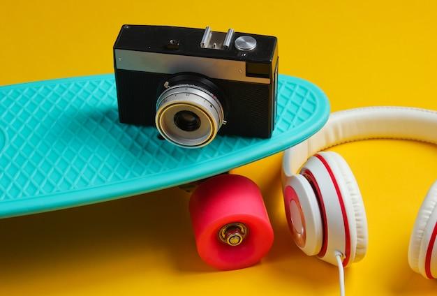 Hipster-outfit. skateboard met koptelefoon op gele achtergrond. creatief mode-minimalisme. trendy retro jaren 80-stijl. minimaal zomerplezier
