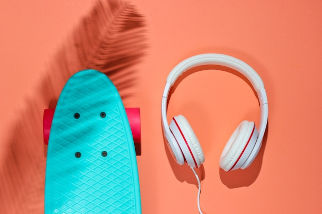 Hipster-outfit. skateboard met koptelefoon op koraal achtergrond met schaduw van palmblad. creatief mode-minimalisme. trendy oude modieuze stijl. minimaal zomerplezier. muziek concept