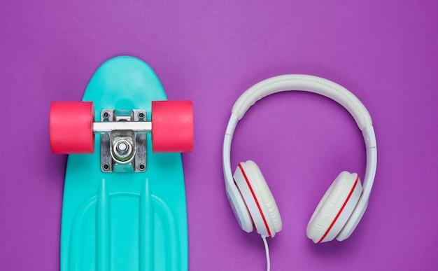 Hipster-outfit. skateboard met koptelefoon op paarse achtergrond. creatief mode-minimalisme. trendy oude modieuze stijl. minimaal zomerplezier. muziek concept